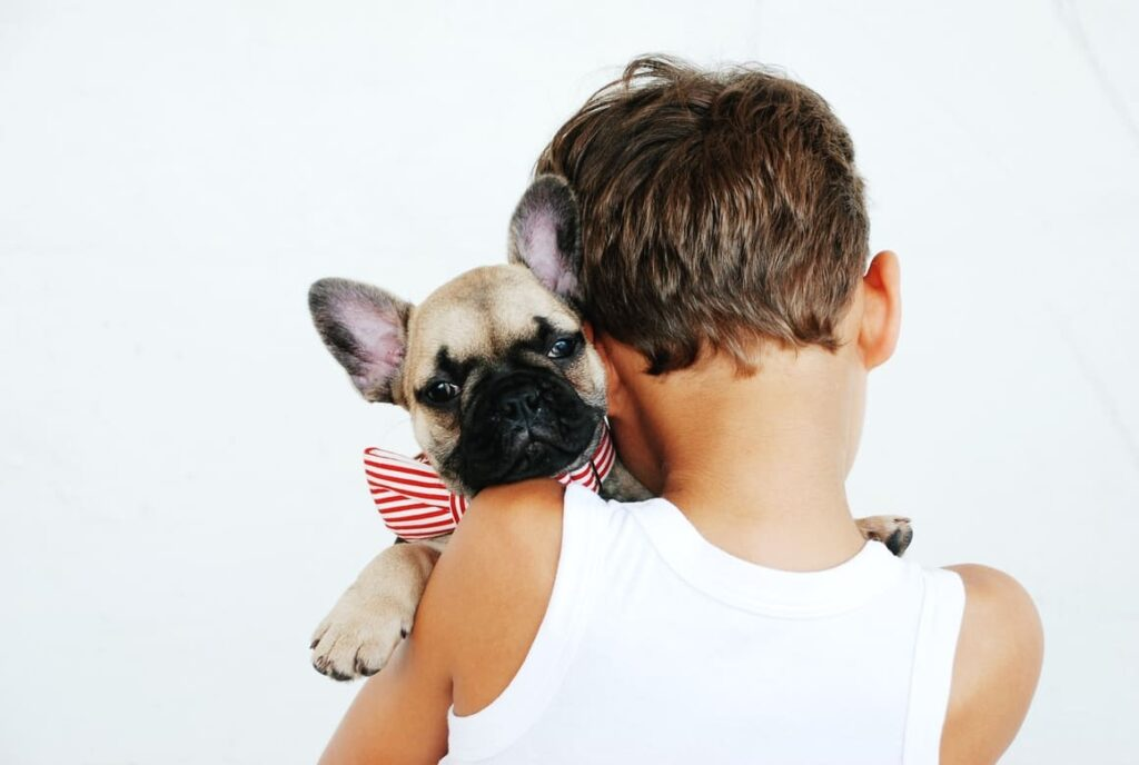Boy holding a puppy on his shoulder trying to decide what name to call her